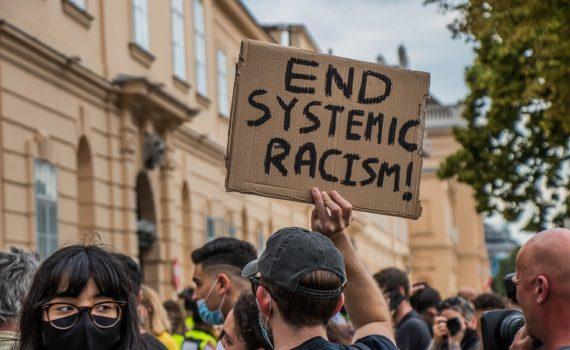 Manifestación con pancartas de Fin del racismo endémico