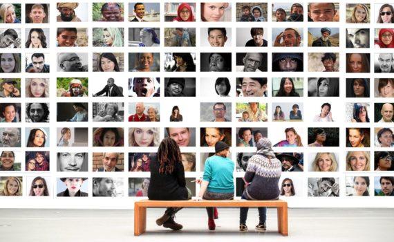 tres personas ante un mural hecho de fotos humanas