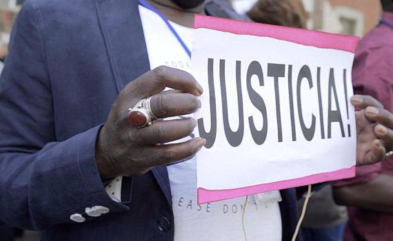 Una mujer sostiene una pancarta con la palabra Justicia