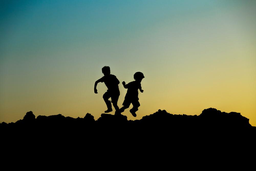 contraluz de dos niños corriendo sobre unas rocas